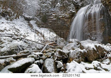Waterfall and rocks during winter in French Alps