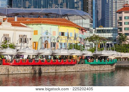 CLARKE QUAY, SINGAPORE - AUGUST 17, 2009: Restaurants at Clarke Quay on the Singapore River with buildings in the background.