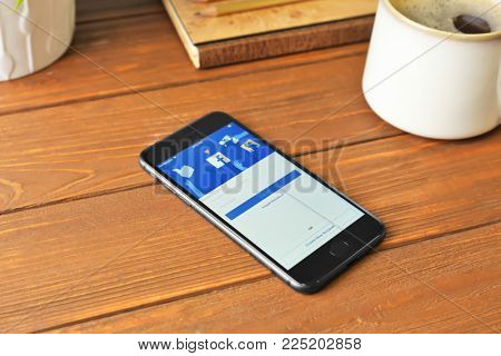 KYIV, UKRAINE - DECEMBER 5, 2017: iPhone 8 Space Grey with Facebook homepage on table