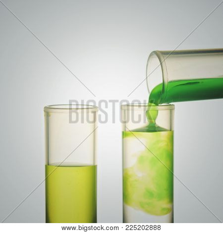 Scientist Hand Pouring A Green Chemical Solution From A Laboratory Glass Test Tube Into A Scientific