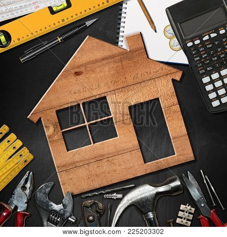 Home improvement concept - Wooden model house on a blackboard with work tools