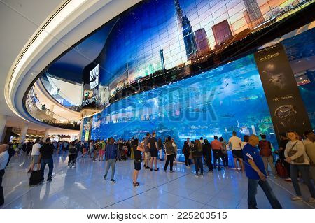 DUBAI, UNITED ARAB EMIRATES - JAN 02, 2018: Tourists are watching at a big aquarium inside the shopping mall in the center of the city near the Burj Khalifa