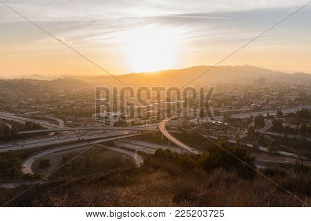 Hilltop view of sunset behind Griffith Park and the Ventura 134 and Glendale 2 freeway interchange in the Eagle Rock neighborhood of Los Angeles California.