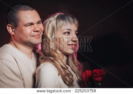 Man and woman in a white dresses lighted colored light in studio and black background