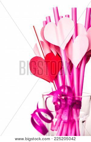 valentine's day holiday. pink and red sipping straws in a glass isolatedon white background.bright sipping straws for party or birthday
