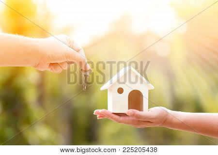 Buying a new house concept, a women and man hand holding a model home and a key put together in the public park.