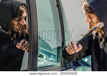 Transportation, crime and ownership concept - Male hooded thief burglar breaking smashing the car window.