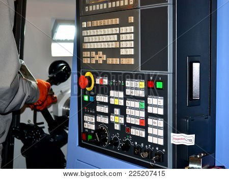 Person works behind the control panel of the production machine at the factory. Industrial production, heavy machinery