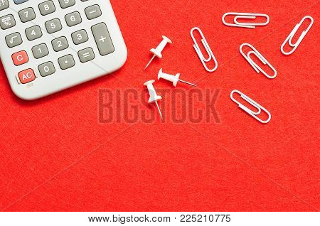 A calculator, pushpins and paperclips displayed on a red background