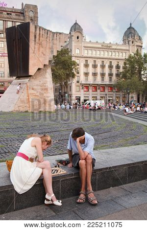 Barcelona, Spain - August 25, 2014: Young man and woman play chess on Catalonia Square, large square in central Barcelona