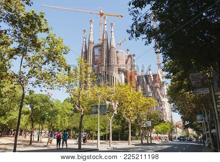 Barcelona, Spain - August 27, 2014: La Sagrada Familia, Catholic cathedral designed by Antoni Gaudi, which is being build since 1882 and still is under construction. Tourists walk on street nearby