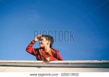 boy gazes into the distance. smiling boy on a background of bright blue sky on a sunny day. Copy space for your text
