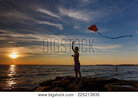 boy launches a kite on the seafront. Child silhouette with a kite on the beach at sunset. Copy space for your text