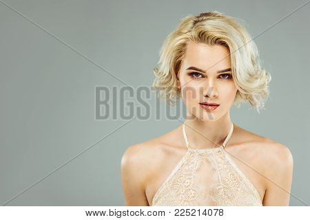 portrait of blonde woman in white lace bra, isolated on grey