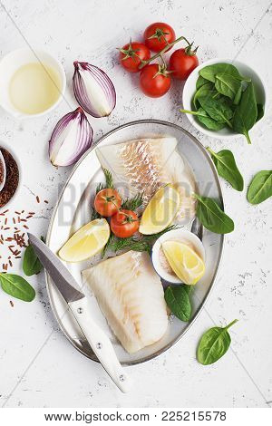 Fresh white sea fish cod fillets on a background with onions, tomatoes, red rice, salt, spinach, ingredients for cooking lunch. Top View