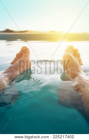 Male Feet In Outdoor Swimming Pool. Man Enjoying Refreshing Poolside Water In Summer Sunset. Holiday