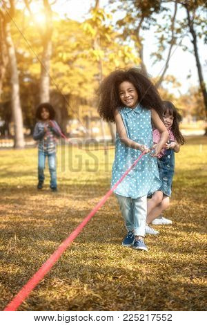 Children are happy to play tug at the park. Soft focus concept.