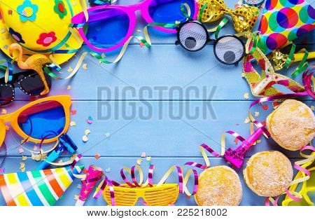 Colorful carnival frame of accessories, streamers, party hat and confetti on blue wooden planks with copy space.