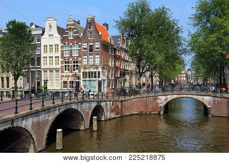 Amsterdam, Netherlands - July 7, 2017: Tourists Visit Keizersgracht And Leidsegracht Canal Crossing