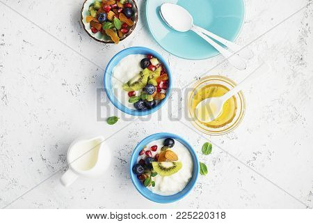 Breakfast, rice porridge or natural yoghurt with assorted berries, fruits and nuts: kiwi, pomegranate, blueberries, almonds, dried apricots in small bowls on a light background. Top view. Copy space