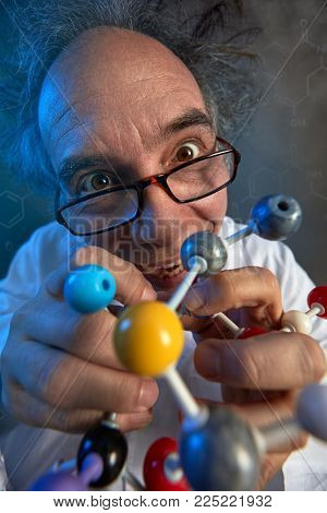 Crazy scientist with model molecules building a new chemical compound