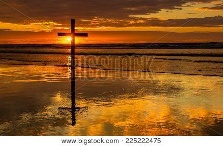 Dark cross on a beach with a wonderful sunset sky.