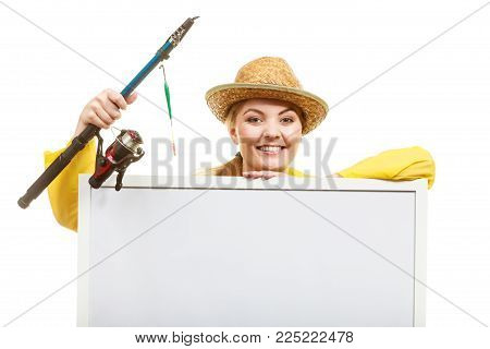 Fishery, spinning equipment, angling sport and activity concept. Happy woman with fishing rod holding blank white board with copyspace.