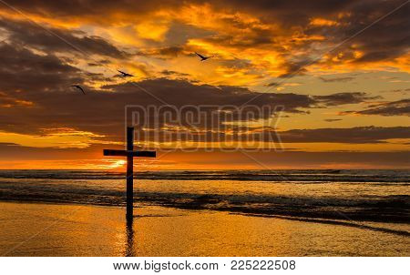 Dark cross on a beach with a wonderful sunset sky ad three sea birds flying over.