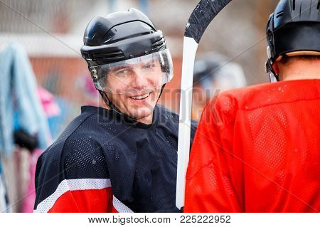 Smiling professional player waiting for substitution in ice hockey competition. Substitute ice hockey forward