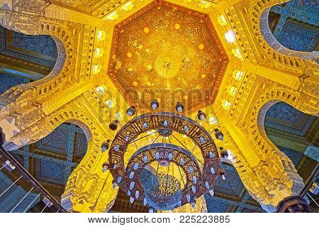 ALEXANDRIA, EGYPT - DECEMBER 17, 2017: The scenic cupola of Abu al-Abbas al-Mursi Mosque with stone arches from the sides and carved wooden decor in the middle, on December 17 in Alexandria.