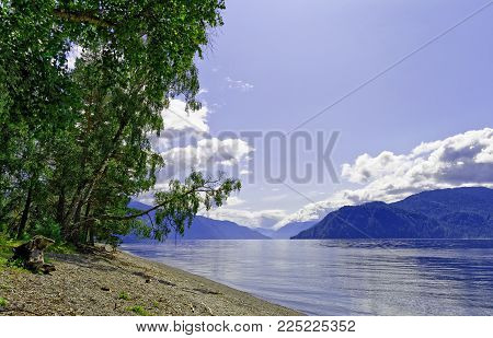 Siberia. Lake Teletskoe. View to the south part and the left bank in summer noon