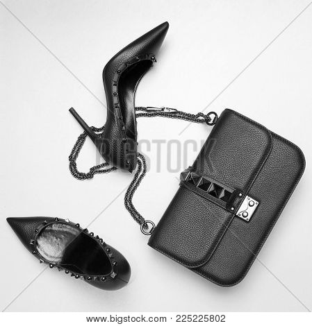 Black fashion shoes and handbag. Fashionable set of accessories from heeled shoes and bags with spikes.