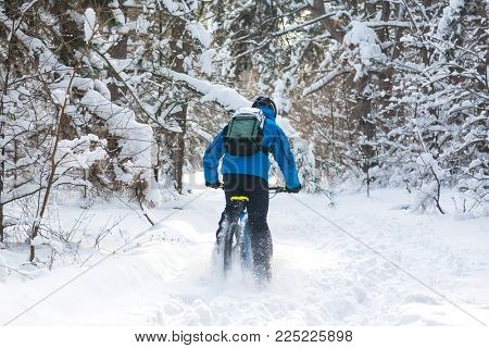 Cyclist in Blue Drifting on the Mountain Bike in the Beautiful Winter Forest Covered with Snow. Extreme Sport and Enduro Biking Concept.