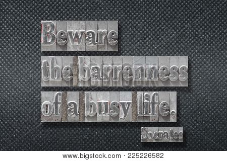 Beware the barrenness of a busy life - ancient Greek philosopher Socrates quote made from metallic letterpress on dark background