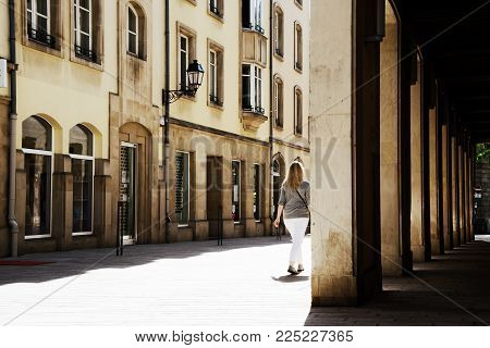 Blond woman goes for a walk in Vienna in summer