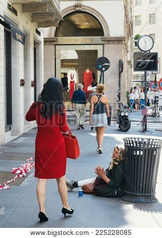 Milan, Italy - July 14th, 2016: Woman Carrying A Luxury Carrier Bag Passing By A Beggar On Via Monte