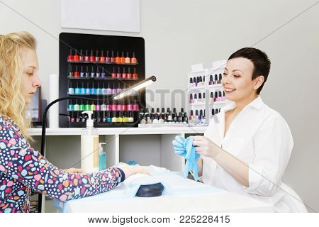 Professional manicurist beautician shaping nails to a young girl in beauty salon poster