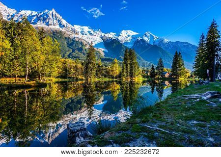 Concept of active and ecotourism. Large stump on the shore of the lake. Snowy Alps are reflected in the lake. Magically beautiful park in the mountain resort of Chamonix