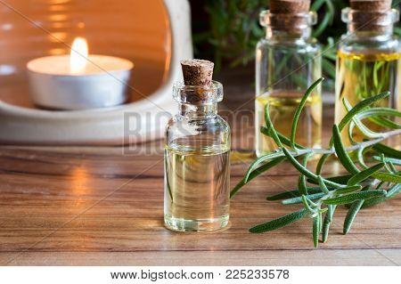 A bottle of rosemary essential oil with fresh rosemary twigs and an aroma lamp