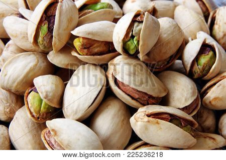 close up image of tasty pistachios nuts as background