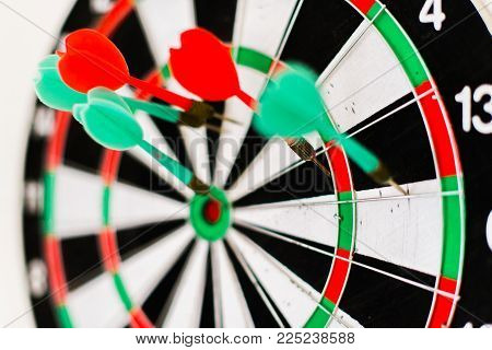 A dartboard target with darts on a white blurred background