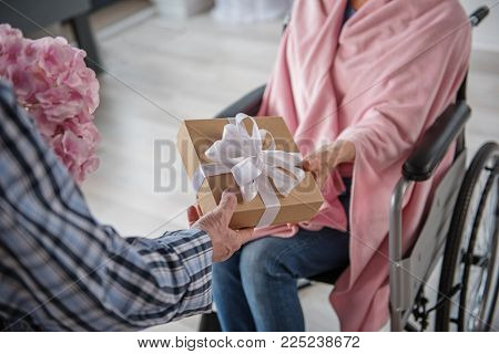 Man Giving A Present To His Wife. She Is Sitting In Wheelchair And He Is Standing Near The Chair And