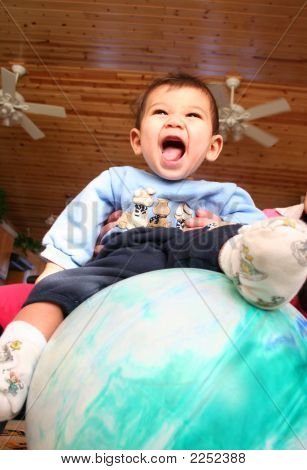 Happy Six Months Old Baby Sitting On Top Of Large Ball