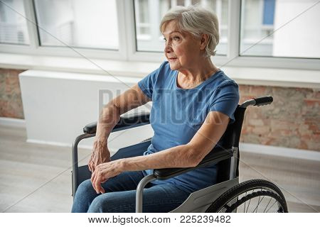 Hopeless Senior Female Sitting In Invalid Chair With Vacant Look. She Is Feeling Upset And Alone