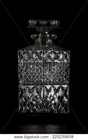 Black and white cut glass whiskey bottle in studio.