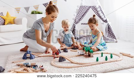 family mother and children play a toy railway in the playroom