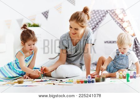 children's creativity. mother and children draw paints in the playroom