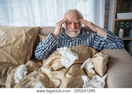 Depressed Senior Man Looking At Camera With Tired Look. He Is Suffering From Migraine At Home And Ho