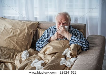 Sick Senior Man Suffering From Illness. He Is Sitting In Bed Covered With Blanket And Blowing His No