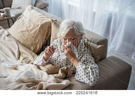 Exhausted Old Female Having Migraine And Blowing Her Nose. She Is Sitting In Bed And Holding Her Hea